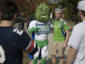 Buddie, the mascot for the pro-marijuana legalization group ResponsibleOhio, poses for photos with passing college students at Miami University, Oct. 23, 2015, in Oxford, Ohio. (Photo: John Minchillo, AP)