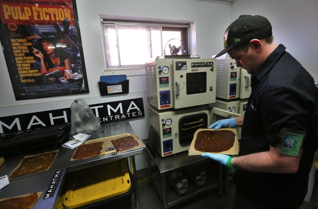 Professional extractor Jeremy Johnson removes a sheet of THC concentrate known as shatter from the oven at Mahatma Concentrates in Denver on May 1, 2014. (Brennan Linsley/Associated Press)