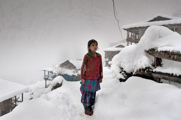 A local girl stares at the mountain peaks after a big snowfall caused her village to lose electricity. PHOTOGRAPH BY ANDREA DE FRANCISCIS