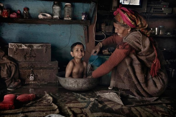 A local woman bathes her grandson in the tandoori (wood stove) room of their house. PHOTOGRAPH BY ANDREA DE FRANCISCIS