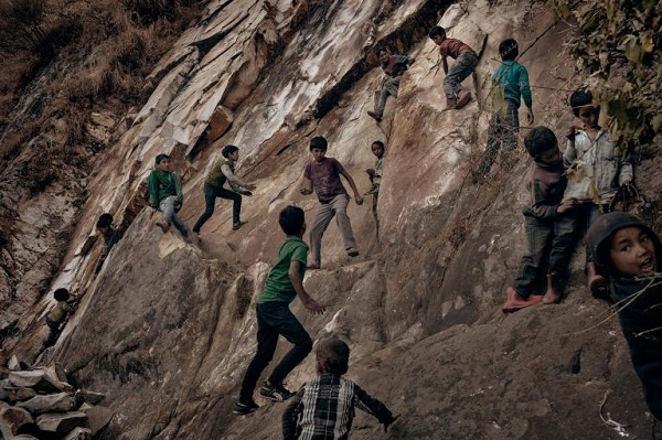 Village children playing on a steep cliff at the outskirts of the village. Families have many children, some are left with older siblings during the day. PHOTOGRAPH BY ANDREA DE FRANCISCIS