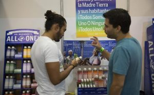 An employee of Dr. Bronner's products, right, speaks with an attendee during the ExpoWeed exhibit at the World Trade Center in Mexico City, Mexico, on Friday, Aug. 12, 2016. (Credit: Susana Gonzalez/Bloomberg)